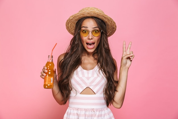Photo of charming woman 20s wearing sunglasses and straw hat drinking soda from glass bottle, isolated over pink wall
