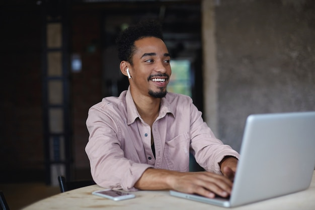 Photo of charming young dark skinned male with short haircut sitting at table and keeping hands on keyboard of his laptop, hearing funny joke and smiling joyfully