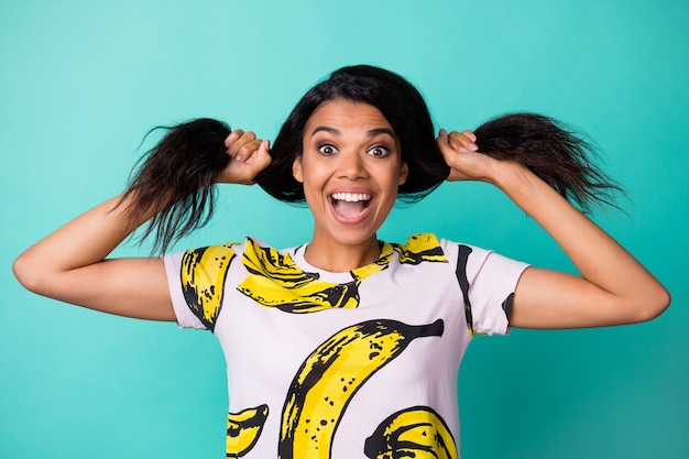 Photo of charming young girl play curly tails open mouth wear banana print t-shirt isolated turquoise color background