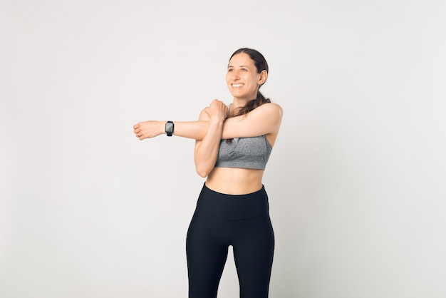 Photo charming young sport fitness woman making stretching over white background