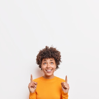 Photo of cheerful african american female points fingers up at top promo text suggests to check out awesome offer demonstrates copy space banner against white wall wears casual jumper.