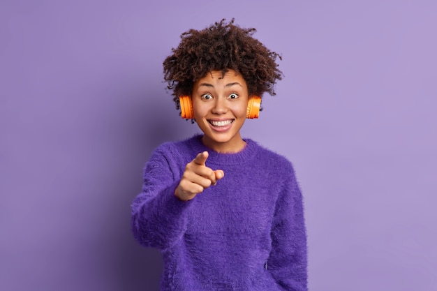 Photo of cheerful african american woman smiles happily and points directly at camera feels very glad chooses you wears headphones on ears listens favorite music