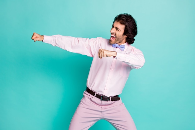 Photo of cheerful brunet curly hair clubber man wear pink shirt dancing stretching fists side looking empty space isolated teal color background