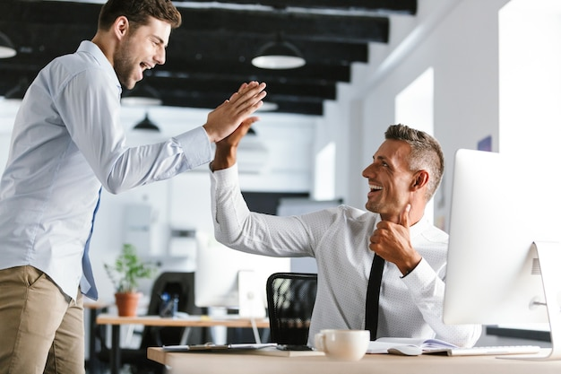 Photo of cheerful businessmen 30s in formal clothes giving high five together in office, during successful deal