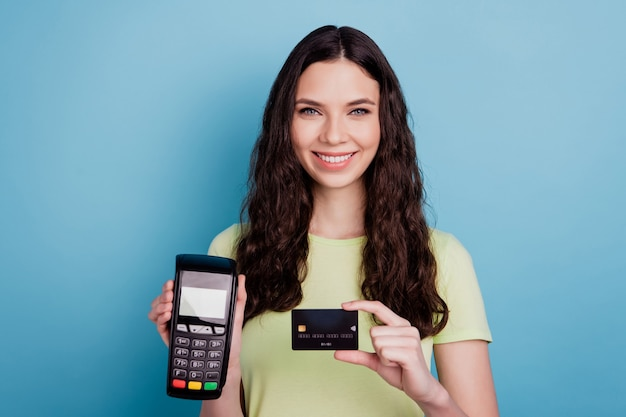 Photo of cheerful cashier lady hold credit card nfc terminal on blue background