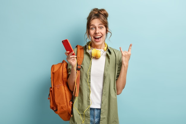 Photo of cheerful caucasian woman makes horn gesture, holds smart phone, listens audio book