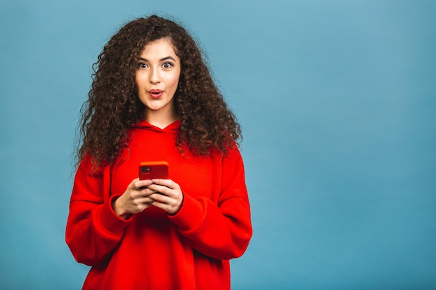 Photo of cheerful cute beautiful young woman chatting by mobile phone isolated over blue wall background. using phone.