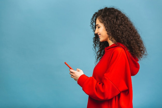 Photo of cheerful cute beautiful young woman chatting by mobile phone isolated over blue wall background.
