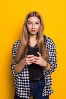 Photo of cheerful cute beautiful young woman chatting by mobile phone isolated over yellow wall wall. looking aside.