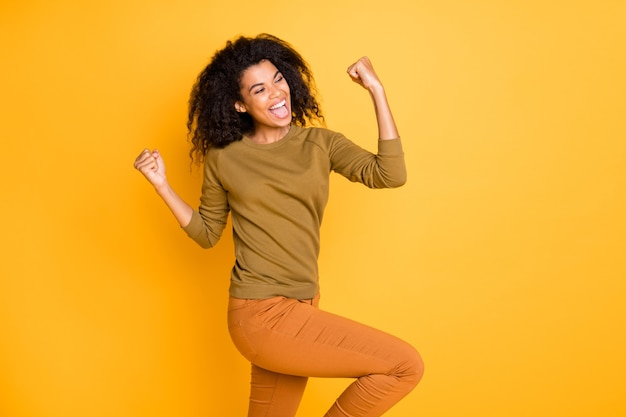 Photo of cheerful cute nice sweet pretty beautiful girl of black skin wearing orange pants trousers screaming shouting yes yeah isolated over vivid color background