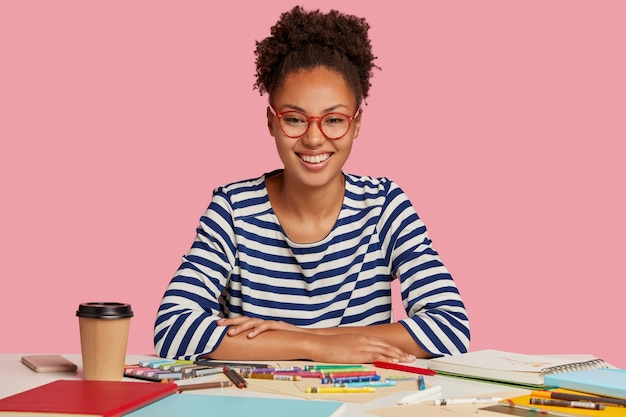 Photo of cheerful dark skinned lady with afro hair combed in pony tail, has toothy smile, being glad with good result of work, creates picture in notepad, wears red rimed spectacles, isolated on pink