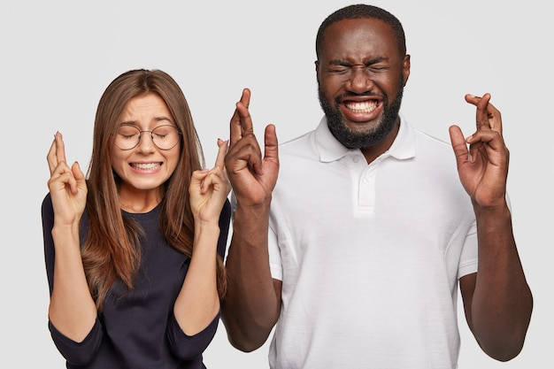 Photo of cheerful dark skinned man, positive european woman cross fingers
