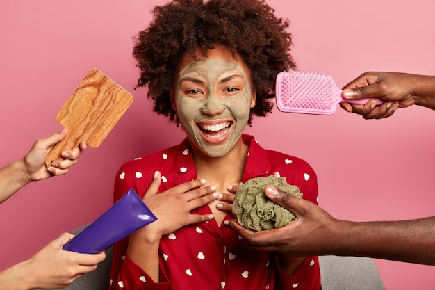 Photo of cheerful dark skinned woman gets pleasure from beauty treatments, has applied clay mask on face, wears pyjama, surrounded by hair comb