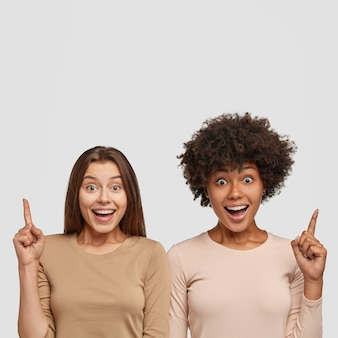 Photo of cheerful dark skinned woman and her female friend, point with index fingers upwards
