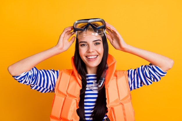 Photo of cheerful excited tourist rescuer girl touch scuba diving goggles enjoy water tourism wear vest white blue striped shirt tube mask isolated over bright shine color background