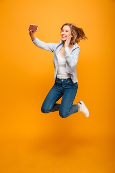 Photo of cheerful excited woman 20s smiling and photographing herself on smartphone, isolated over yellow space