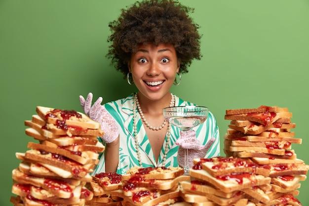 Foto di una donna allegra alla moda con i capelli afro vestita con un vestito elegante, sorride ampiamente, trascorre il tempo libero alla festa, ha una piacevole conversazione con il collega, circondata da una pila di pane