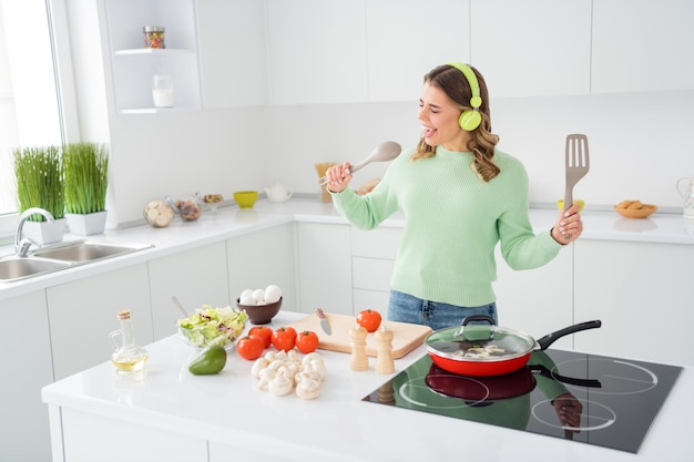 Photo of cheerful funny lady cooking tasty dinner listening headphones music