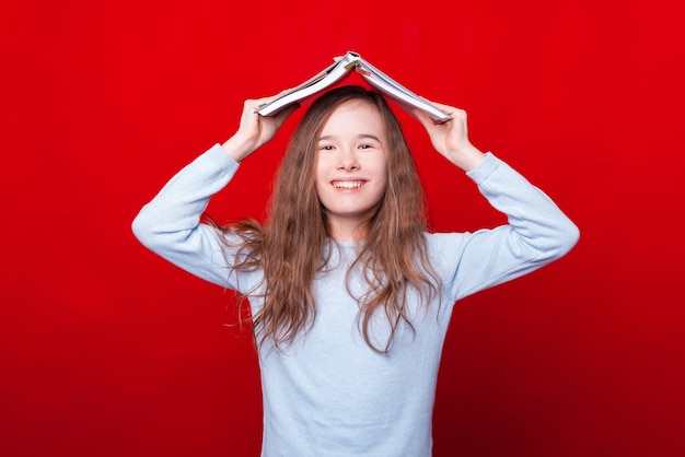 Photo of cheerful girl holding planner or agenda over head on red wall and smiling