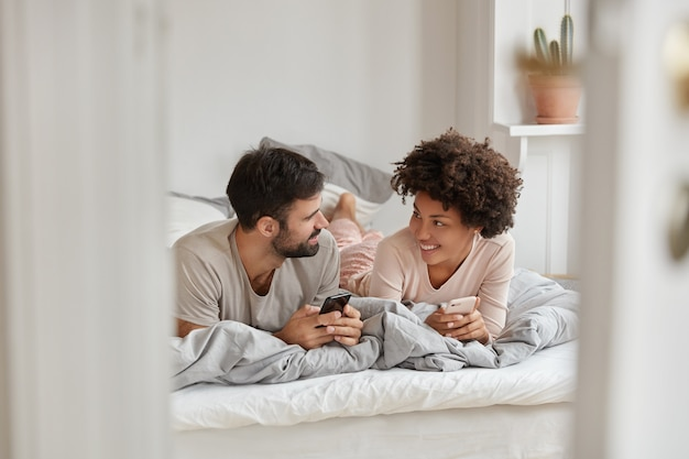 Photo of cheerful girlfriend and boyfriend search hotel for staying during holidays, browse application on smart phone, chat with friends, enjoy comfort in bedroom. modern technologies concept