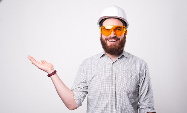 Photo of cheerful handsome architect man wearing helmet and protective glasses holding copyspace in palm