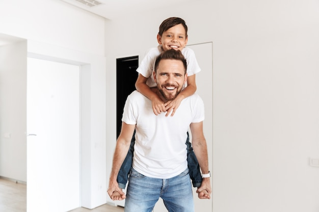 Photo of cheerful happy father piggybacking his son, while resting in white bright apartment