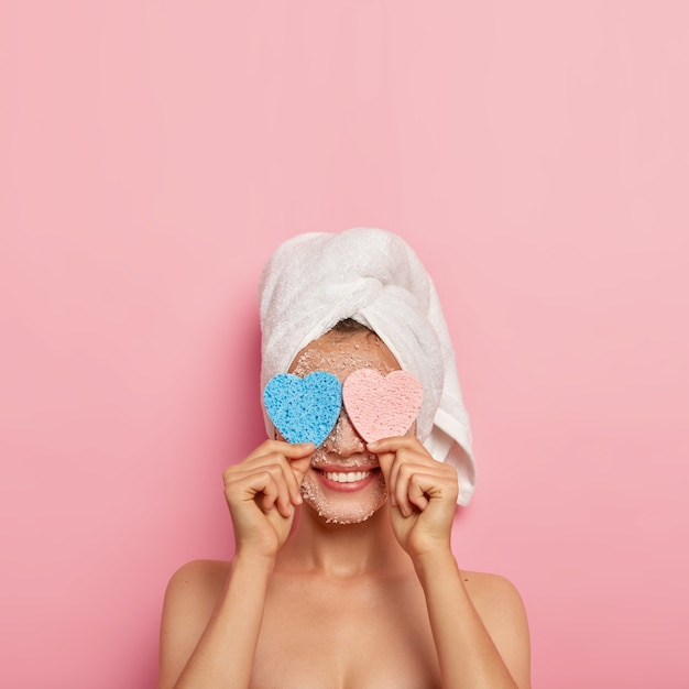 Photo of cheerful healthy european woman keeps two sponges on eyes, hides face and smiles happily, takes bath, has naked body, models over pink background, copy space