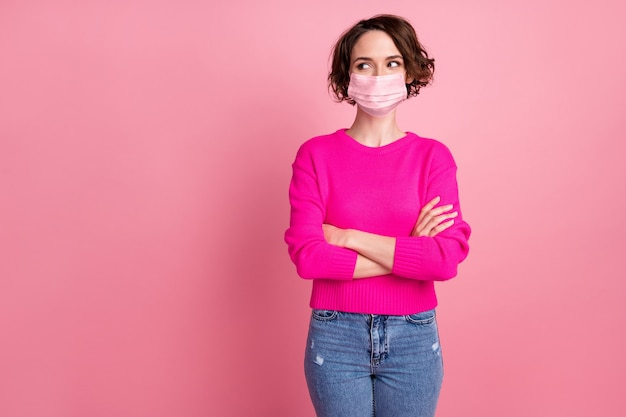 Photo of cheerful lady silly tricky expression arms crossed good mood look side empty space interested wear medical mask casual pullover jeans isolated pink pastel color background