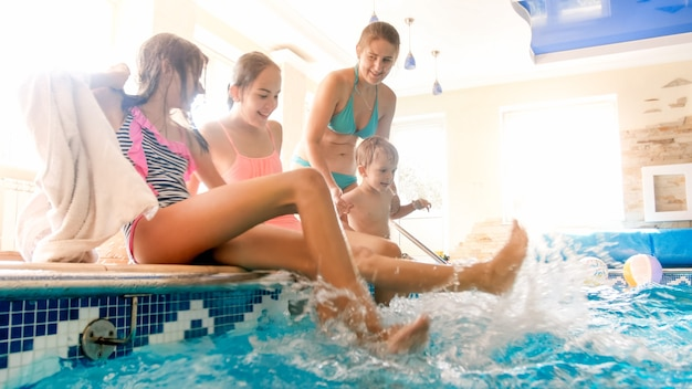 Photo of cheerful laughing family with children splashing water with feet at indoors swimming pool. family playing and having fun at swimming pool