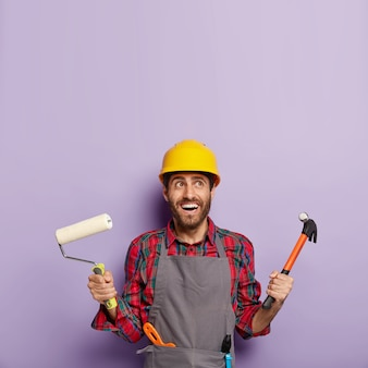 Photo of cheerful male builder or decorator holds hammer and paint roller, ready for painting walls and repairing, has glad expression, looks above.