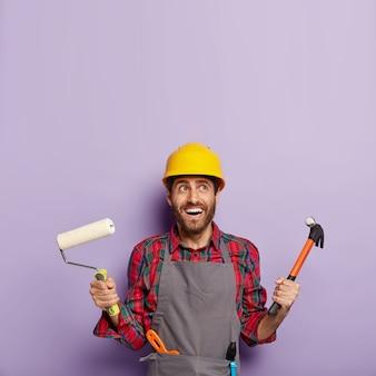 La foto del costruttore o del decoratore maschio allegro tiene il martello e il rullo di vernice, pronto per dipingere le pareti e riparare, ha un'espressione felice, guarda sopra.