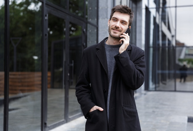 Photo of cheerful man 20s talking on cell phone, while walking outdoor near glass building