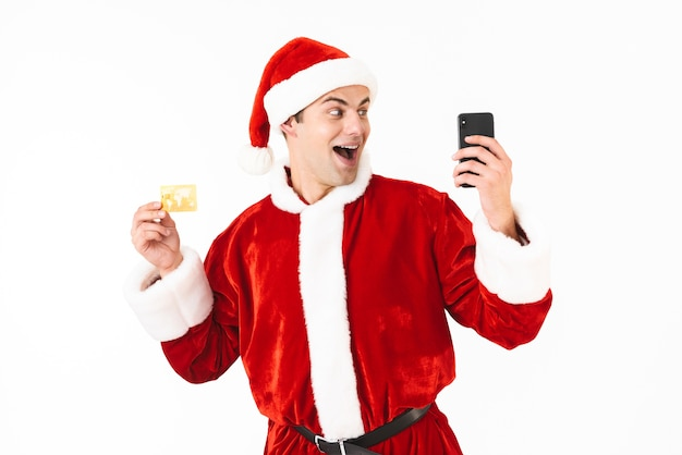 Photo of cheerful man 30s in santa claus costume holding smartphone and credit card