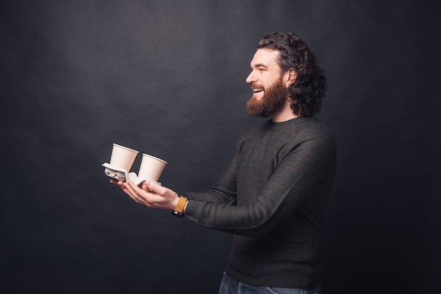Photo of cheerful man in casual giving  two cups of coffee to go