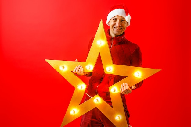 Photo of cheerful man in santa's cap with christmas star garland in hands
