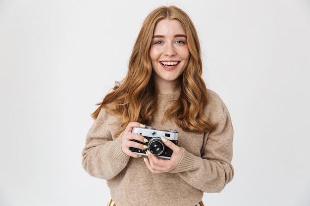 Photo of a cheerful pleased cute young teenage girl posing isolated over white wall wall holding camera photographing.