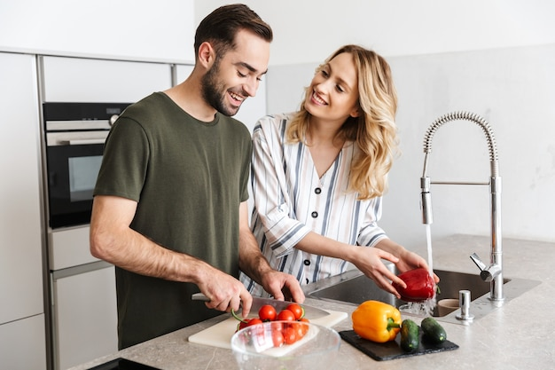 Photo of a cheerful pleased young loving couple indoors at the kitchen cooking vegetable salad have a breakfast.