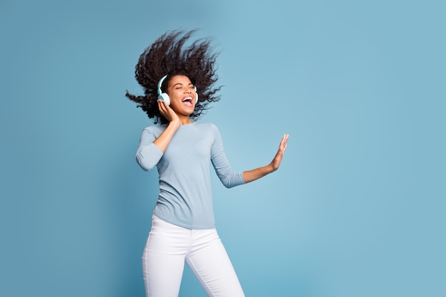 Photo of cheerful positive cute nice pretty girlfriend inspired with her favorite rock band in white pants blue sweater near empty space singing with hair blown isolated pastel color background