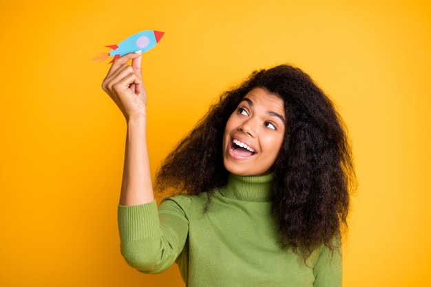 Photo of cheerful positive cute pretty childish youngster playing paper rocket looking excited isolated vivid color background