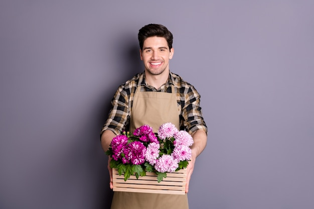 Photo of cheerful positive man smiling toothily working as florist delivering flowers ordered giving them to yous isolated grey color wall