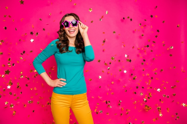 Photo of cheerful positive nice pretty fascinating girlish feminine youngster holding eyeglasses spectacles in yellow pants trousers isolated bright color fuchsia background