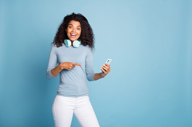 Photo of cheerful positive nice pretty girlfriend smiling toothily pointing at her telephone with astonishment on face in white pants isolated pastel blue color background