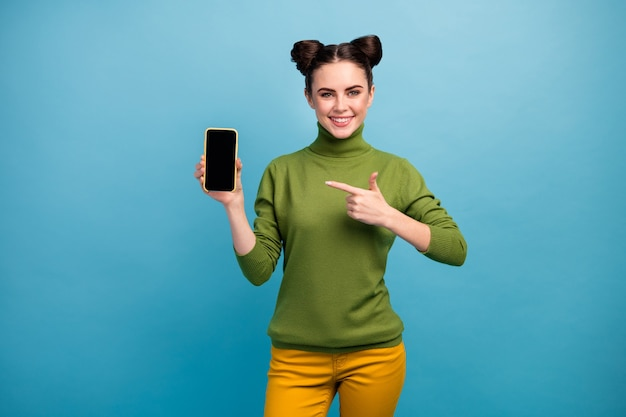 Photo of cheerful pretty lady hold new model smart phone showing presenting advertising amazing quality device wear green turtleneck yellow pants isolated blue color wall