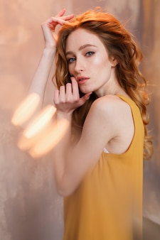 Photo of cheerful redhead young woman in mustard dress and jeans