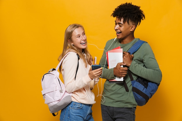 Photo of cheerful students man and woman 16-18 wearing earphones using mobile phones and holding exercise books, isolated over yellow background