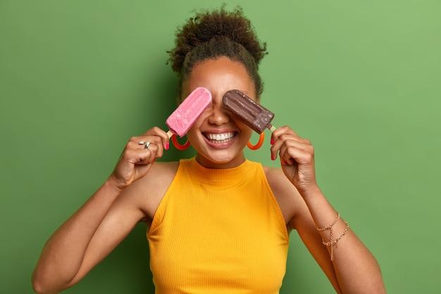 Foto di un'adolescente allegra ha i capelli ricci sorriso a trentadue denti si gode la vita copre gli occhi con due deliziosi gelati indossa una maglietta gialla casual si sente felice durante la giornata estiva isolata sul muro verde
