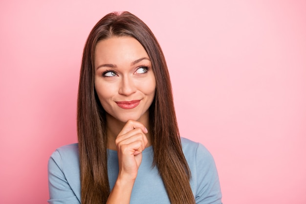 Photo of cheerful trendy cute fascinating lovely girl touching her chin looking up into empty space isolated pastel colo background