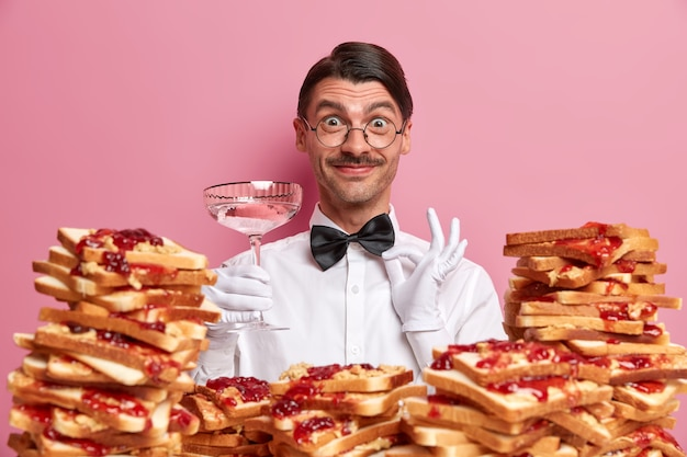 Photo of cheerful waiter in uniform, poses with glass , ready to take order from restaurant visitors, stands against rosy wall with pile of delicious appetizing bread toasts.