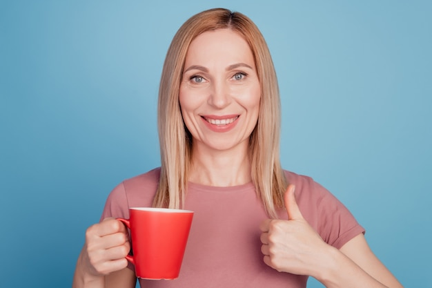 Photo of cheerful woman holding mug of coffee show thumb-up like cool advert isolated over blue color background
