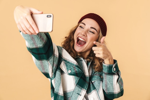 Photo of cheerful woman in knit hat taking selfie on cellphone and pointing finger isolated on beige
